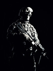 Special operations forces soldier, counter terrorism squad fighter, security service guard, marine shooter in combat uniform, armed with light machine gun low light studio shot on black background