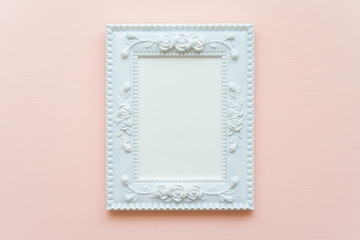 White vintage photo frame on pink pastel wooden background flat lay top view style
