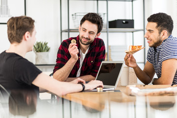 Man eating pizza while his friend holding gold coin of cryptocurrency - BitCoin