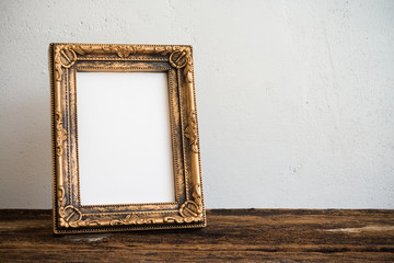 Vintage photo frame on old wooden table over white wall background