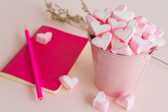 Fluffy pink heart marshmallow in small tank and pink notepad, pencil on pink background
