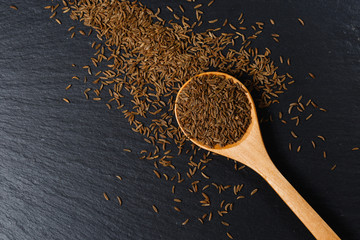 Cumin spice in wooden spoon on dark stone table
