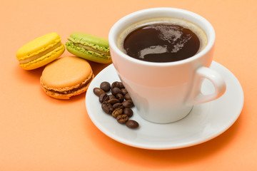 Cup of coffee with coffee beans and delicious macarons cakes of different color on peach background