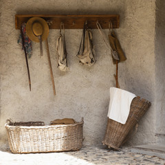 Front view of a retro style outdoor wardrobe with walking sticks, backpacks, baskets and travel equipment.