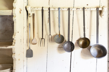 Retro style set of different wooden and metal kitchen spoons and tools hanging on a wall