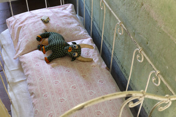 Concept of a sad and poor childhood. Worn old handmade stuffed animal lying on a small rickety bed in a somber room.