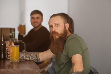 Young man with friends drinking beer in sport bar