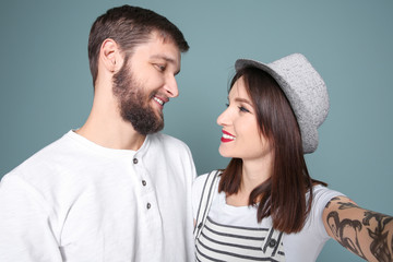 Trendy hipster couple taking selfie against grey background