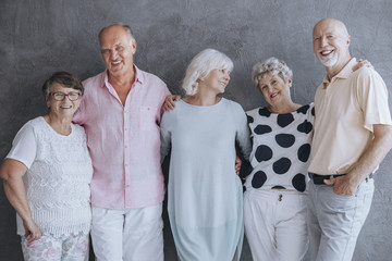 Smiling senior people having fun against concrete wall