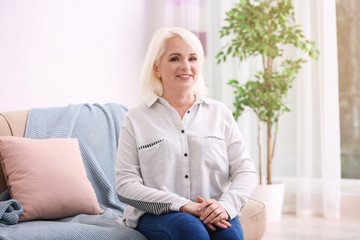 Attractive mature woman sitting on sofa at home