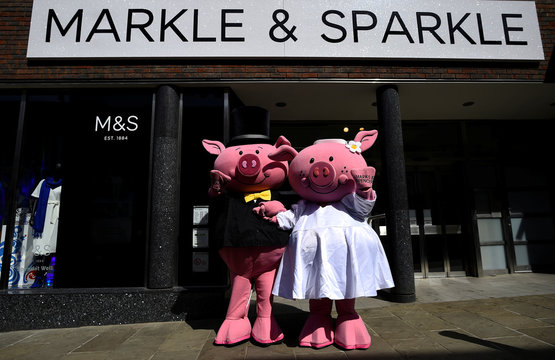 People dressed in cartoon pig costumes pose for photographs in front of an M&S store, during a media event, in Windsor