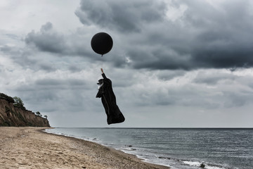 Plague doctor fly in a hot air balloon . Outdoor portrait with dramatic sky in background.