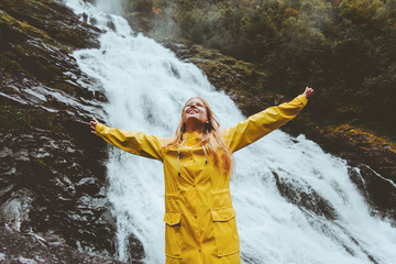Young woman traveling at waterfall emotional raised hands adventure healthy lifestyle harmony with nature concept girl wearing yellow raincoat walking alone