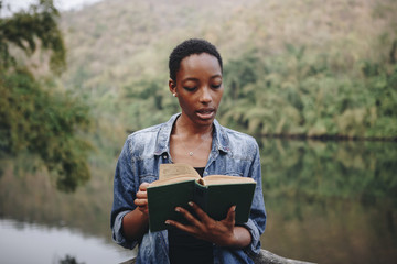 African American woman alone in nature reading a book leisure concept
