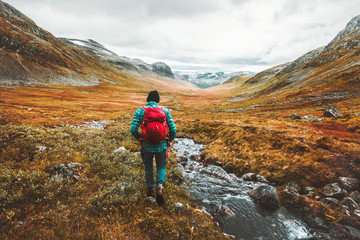 Traveling Man tourist with backpack hiking in mountains landscape active healthy lifestyle adventure vacations in Scandinavia