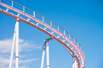 Pink pastel looping roller coaster on blue sky sunny day