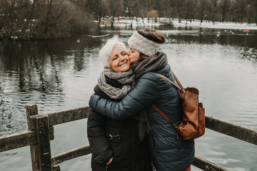 .Mother and daughter enjoying a trip to sweden. Trekking activity in front of a nice and quiet lake. Cold spring day. Lifestyle photography.