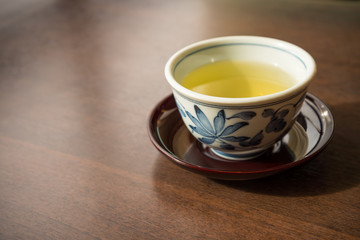 A ceramic cup of traditional Japanese tea on wooden table
