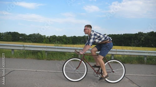 Young handsome man riding at vintage bicycle in the country road