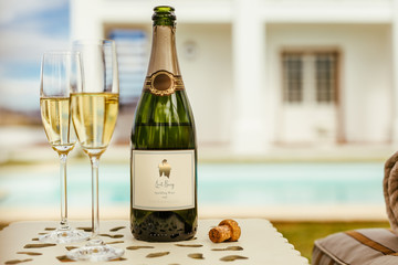 Two glasses of sparkling wine with bottle at the poolside