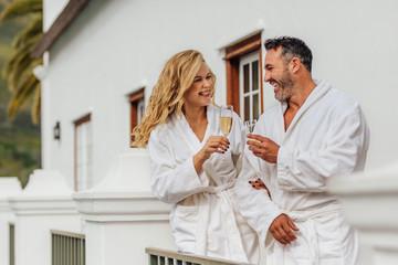 Beautiful couple in bathrobe having wine