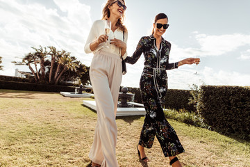 Stylish women walking together and smiling.