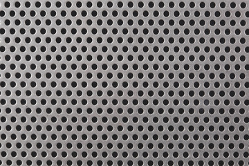 close up on a mettalic texture with small holes