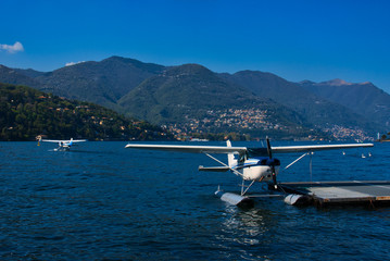 Seaplane moored at a jetty with another seaplane and Lake Como in the background
