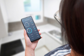 Woman use smart home control app on modern mobile phone. Home interior in background.