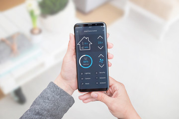 Smart home control app for mobile devices in woman hand. Living room interior in background.