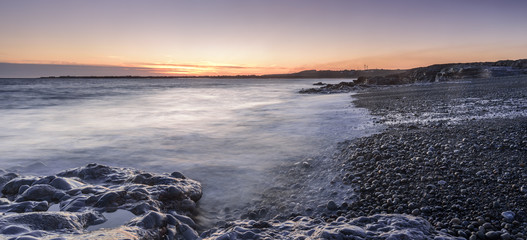 Sunset off the South Wales coast. Ogmore-by-Sea is a popular destination to swim and surf. A long shutter speed has been used to create a milky sea effect