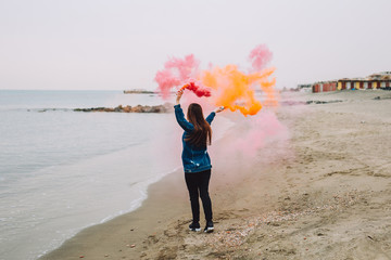 Young girl holds in her hand colorful smoke of many colors near the sea
