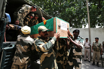 India's Border Security Force (BSF) soldiers carry a casket containing the remains of their colleague before his wreath-laying ceremony on the outskirts of Jammu