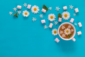 Cup of tea with marshmallows and flowers blossom  bouquets on blue surface