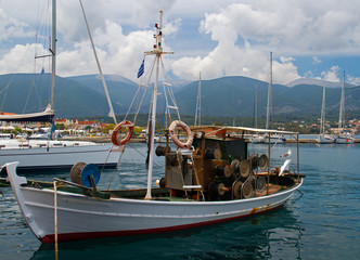 Small white fishing boat in the harbour of Fiskardo on the ionian island Kefalonia in Greece