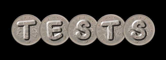 TESTS written with old British coins on black background