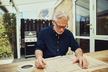 Stern senior man reading a financial newspaper at home