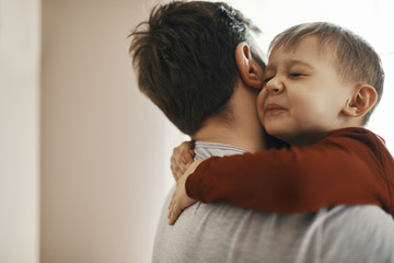 Portrait of toddler hugging his father