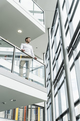 Businessman in office leaning on railing