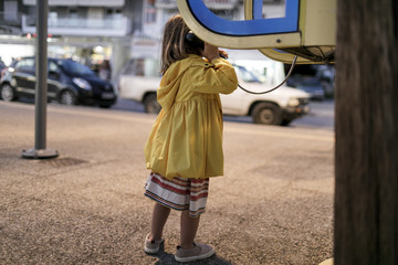 Back view of little girl using telephone booth