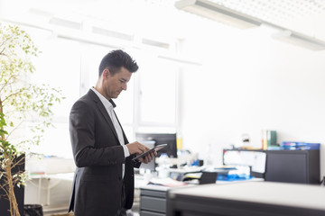 Successful businessman standing in office, using digital tablet
