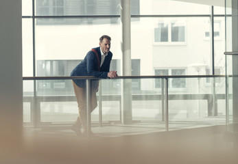 Businessman in office building leaning on railing