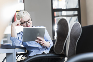 Smiling woman using tablet in office