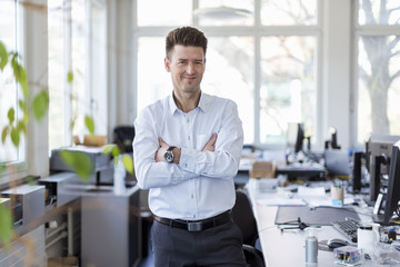 Portrait of a successful businessman standing in office with arms crossed