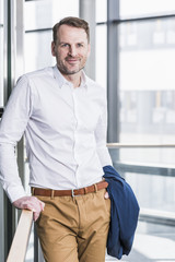 Portrait of smiling businessman standing