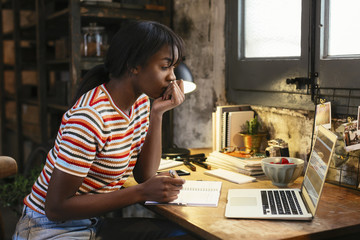 Pensive young woman sitting at desk in a loft looking at laptop