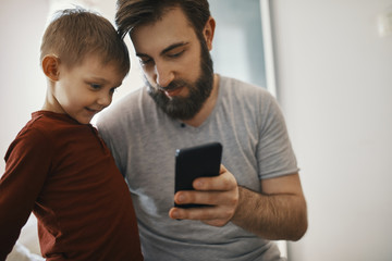 Father explaining little son smartphone