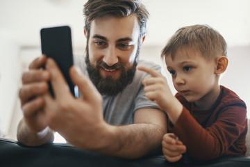Portrait of father and little son with smartphone