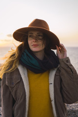 Italy, Sardinia, portrait of woman at the coast at sunset