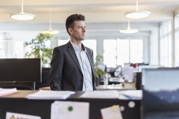 Portrait of a successful businessman standing in office, looking serious
